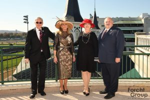 2 women and 2 men standing in the sun shine with the twin spires behind them