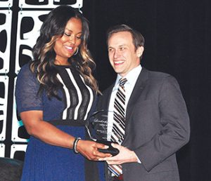 Forcht: a woman in a navy dress handing an award to a man in a suit