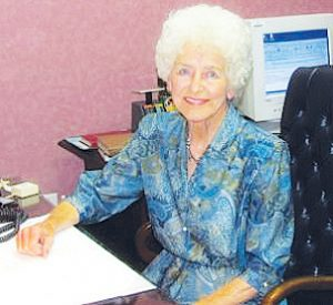 Treasure: a woman in a blue dress sitting at a desk smiling at the camera